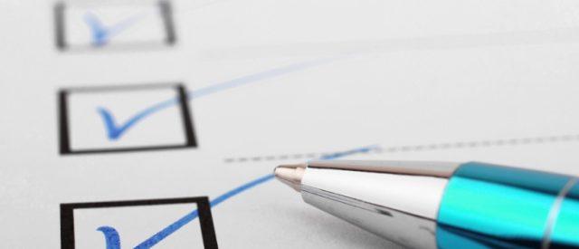 Bilden visar en penna som ligger på ett papper med ifyllda rutor.